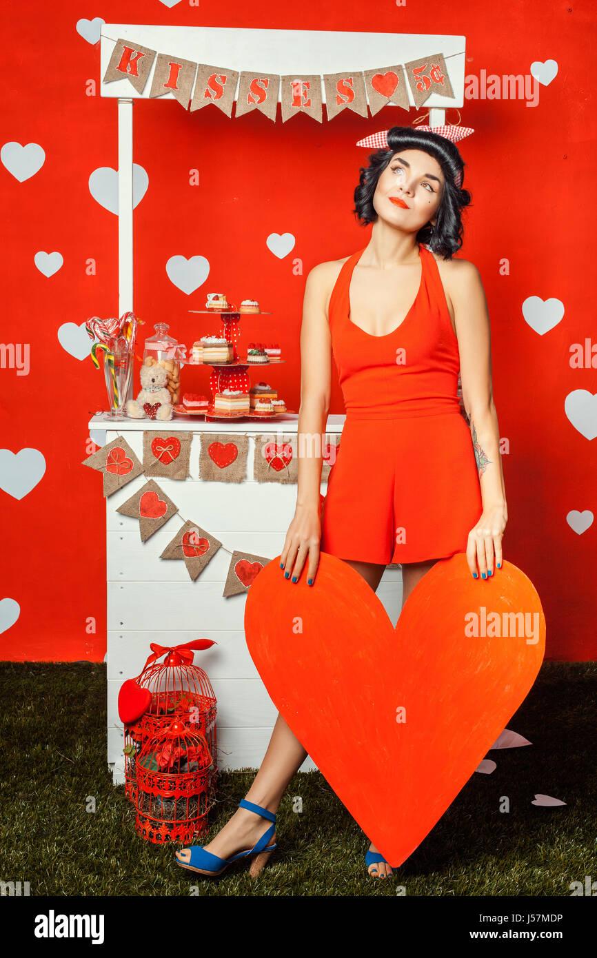 Pin-up girl ritratto, ragazza e permanente tenendo un cuore rosso realizzato in carta, la sua testa sollevata e Immagini Stock