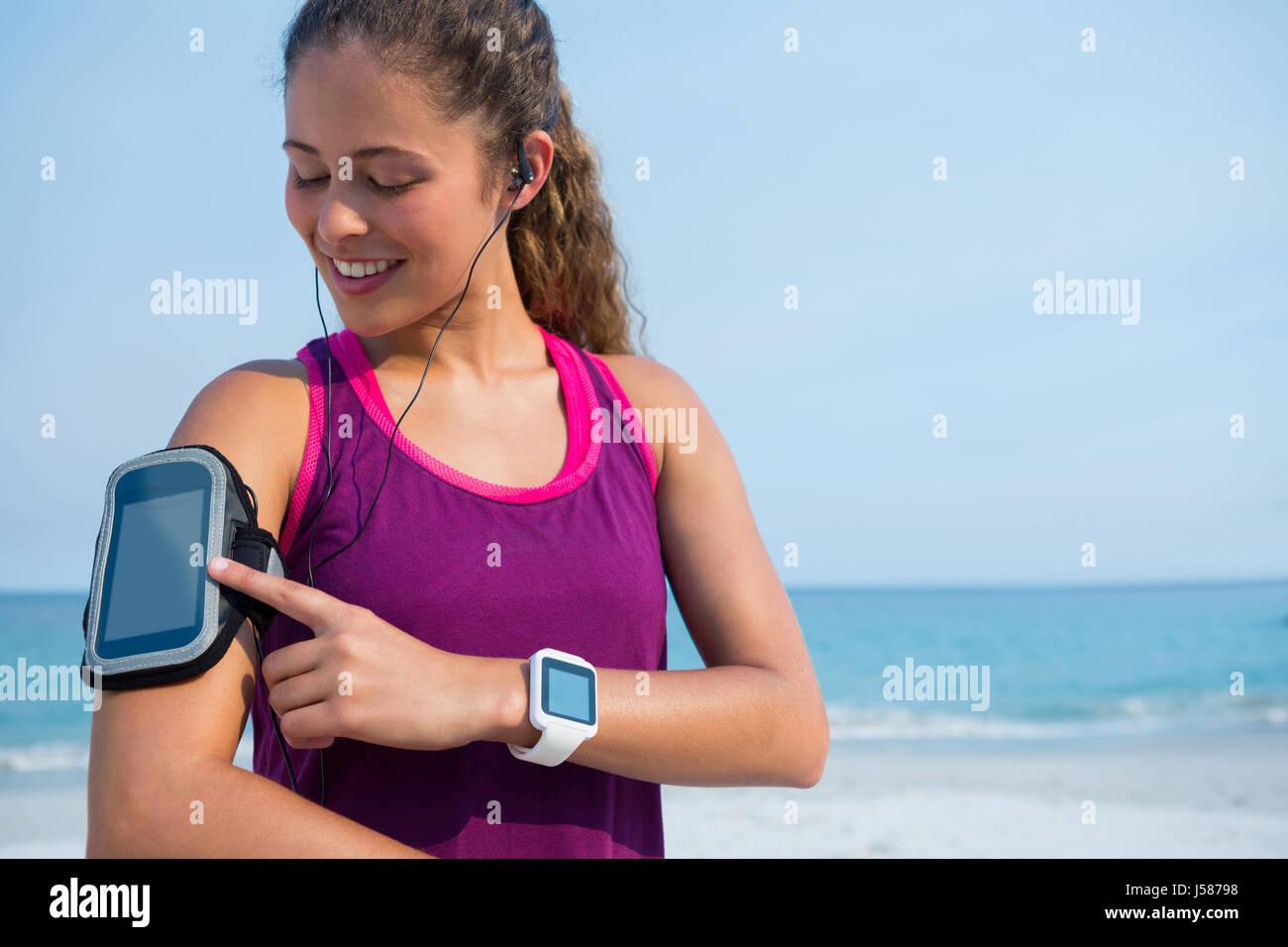 Sorridente giovane donna toccando fascia braccio contro il cielo blu a beach Immagini Stock