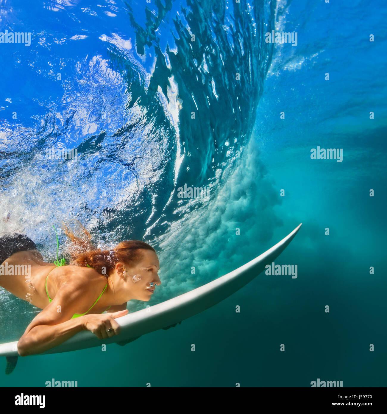 Active Ragazza in Bikini in azione. Surfer donna con tavola da surf subacquea Immersioni sotto la rottura grande Immagini Stock