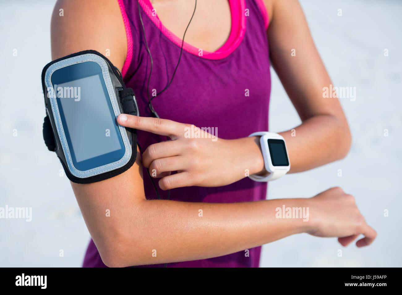 La sezione centrale della donna che indossa fascia braccio e smart guarda alla spiaggia Immagini Stock