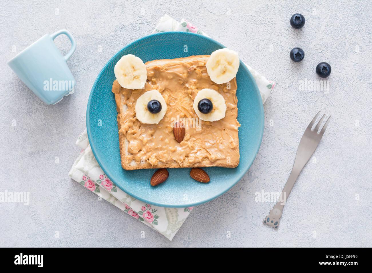 Burro di arachidi toast per bambini in forma di divertente carino gufo su una piastra di blu. Vista superiore Immagini Stock