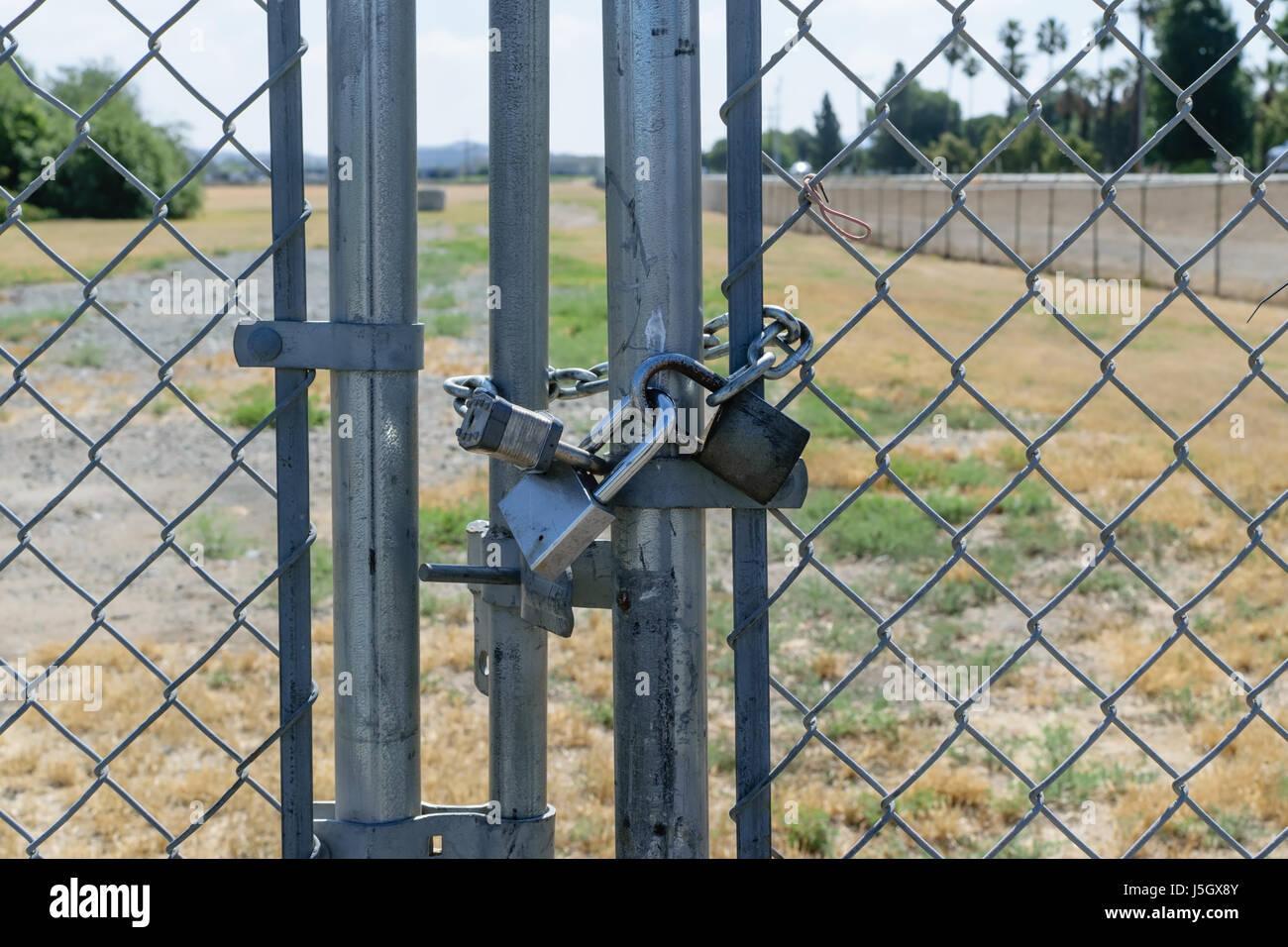 Tre serrature porta sicura sulla recinzione Immagini Stock