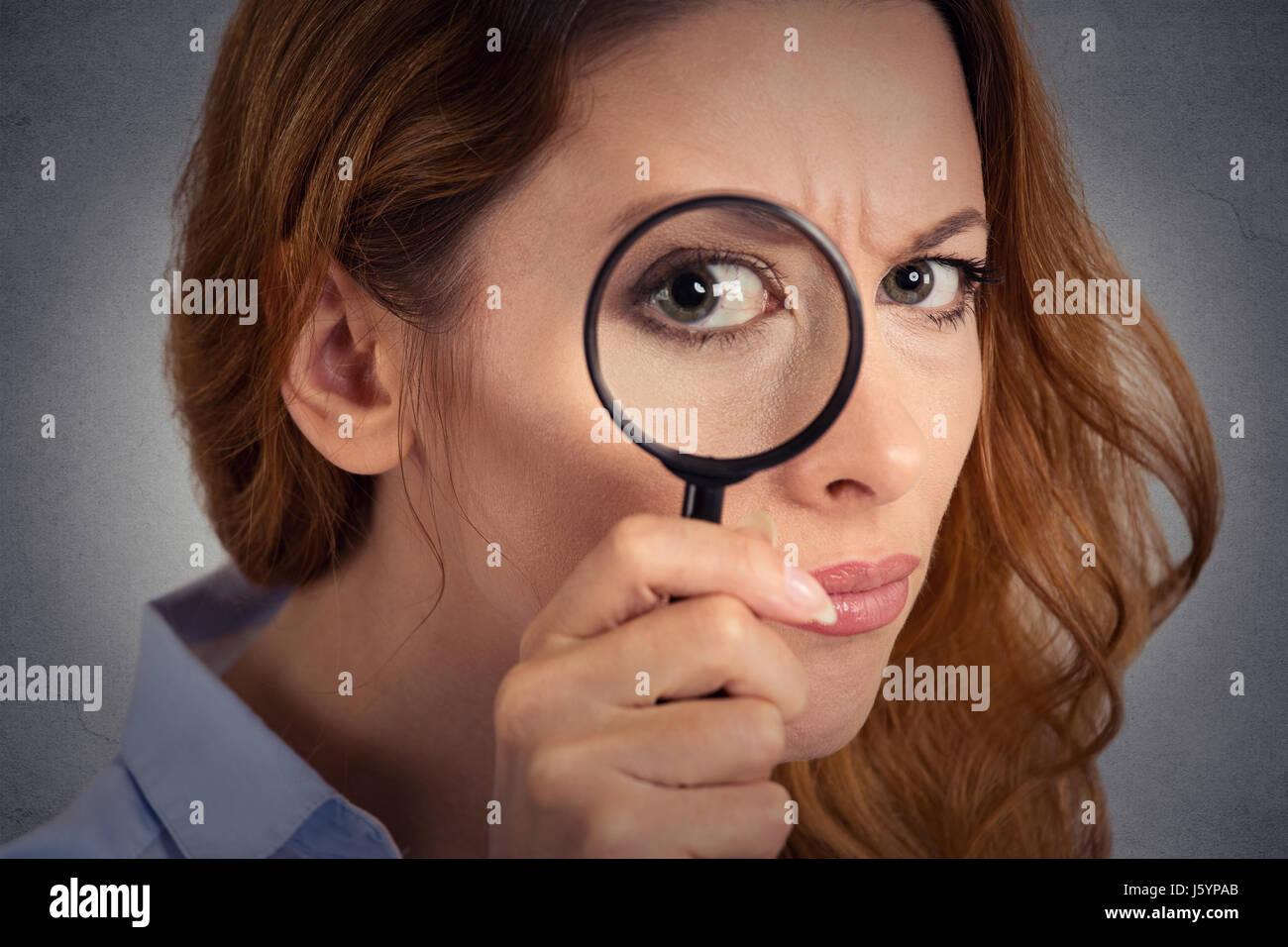 Headshot donna investigatore guardando attraverso la lente di ingrandimento Immagini Stock