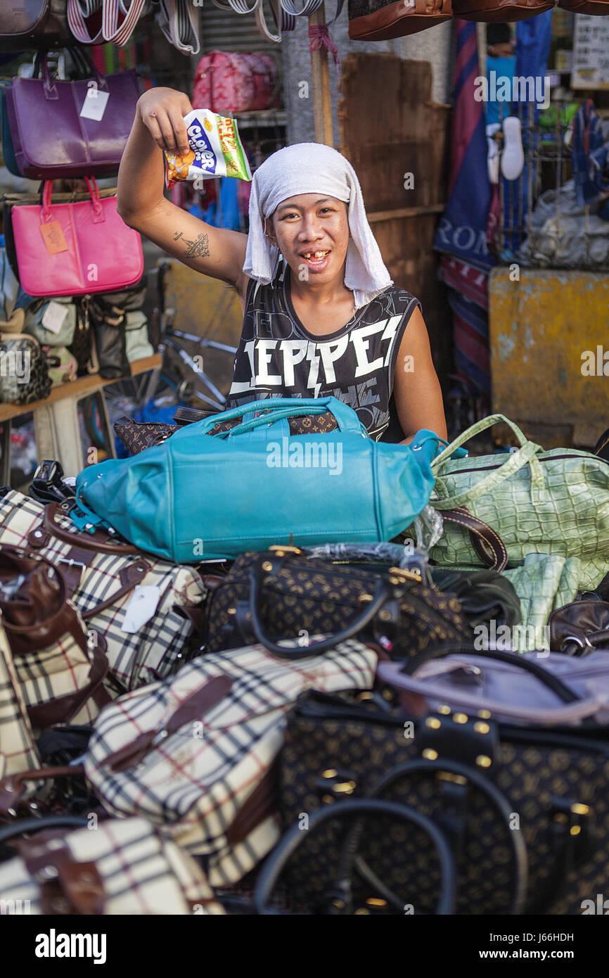 Uomo filippino vende falso nome del marchio sacchetti a Baclaran la strada del mercato di Parañaque City, Metro Immagini Stock