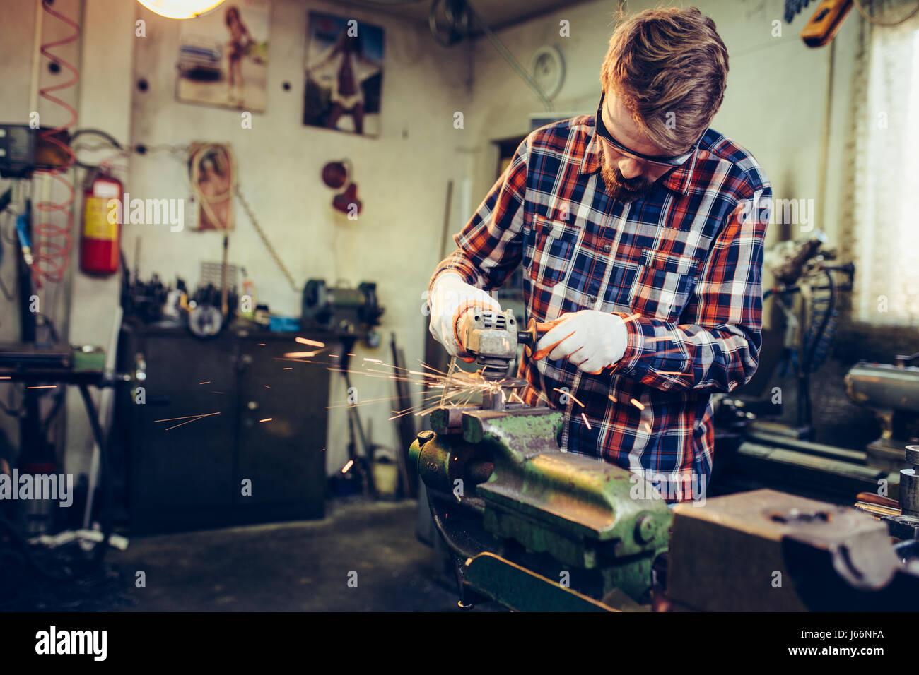 Giovane lavoratore manuale lavora con la fresa Immagini Stock