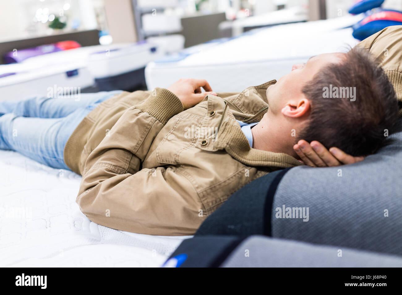 Giovane uomo che sta provando che stabilisce il materasso sul display in negozio Immagini Stock