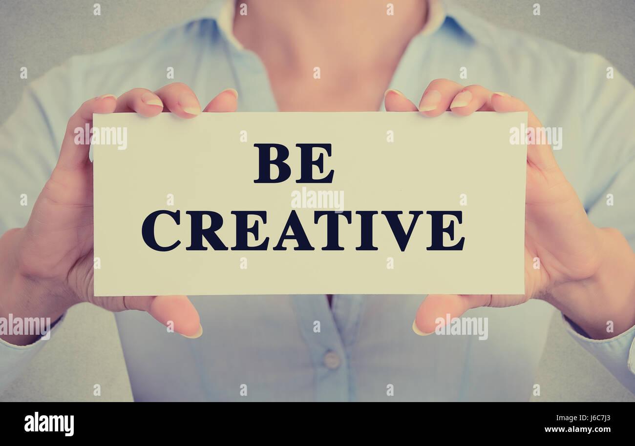 Closeup imprenditrice mani carta bianca segno di essere creativi messaggio di testo isolato sul muro grigio office Immagini Stock
