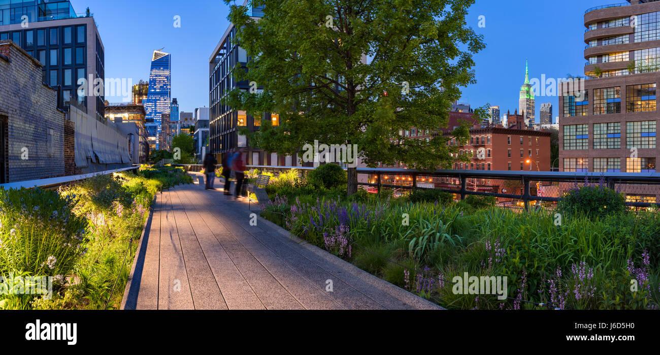 Highline vista panoramica al crepuscolo con le luci della città illuminata di grattacieli e grattacieli. Chelsea, Immagini Stock