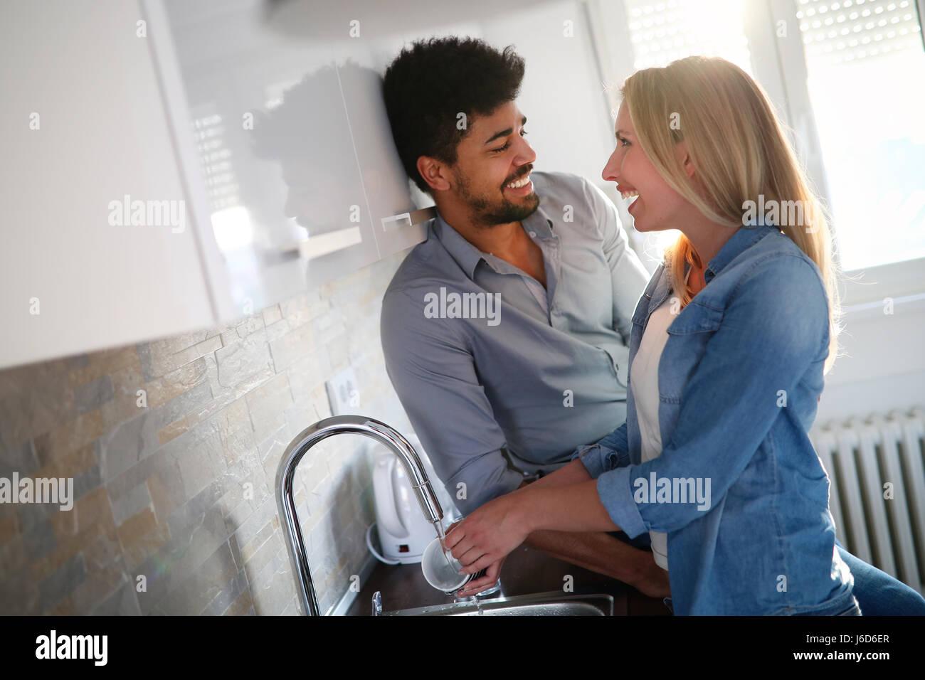 Coppia giovane in amore facendo i piatti in cucina e sorridente Immagini Stock