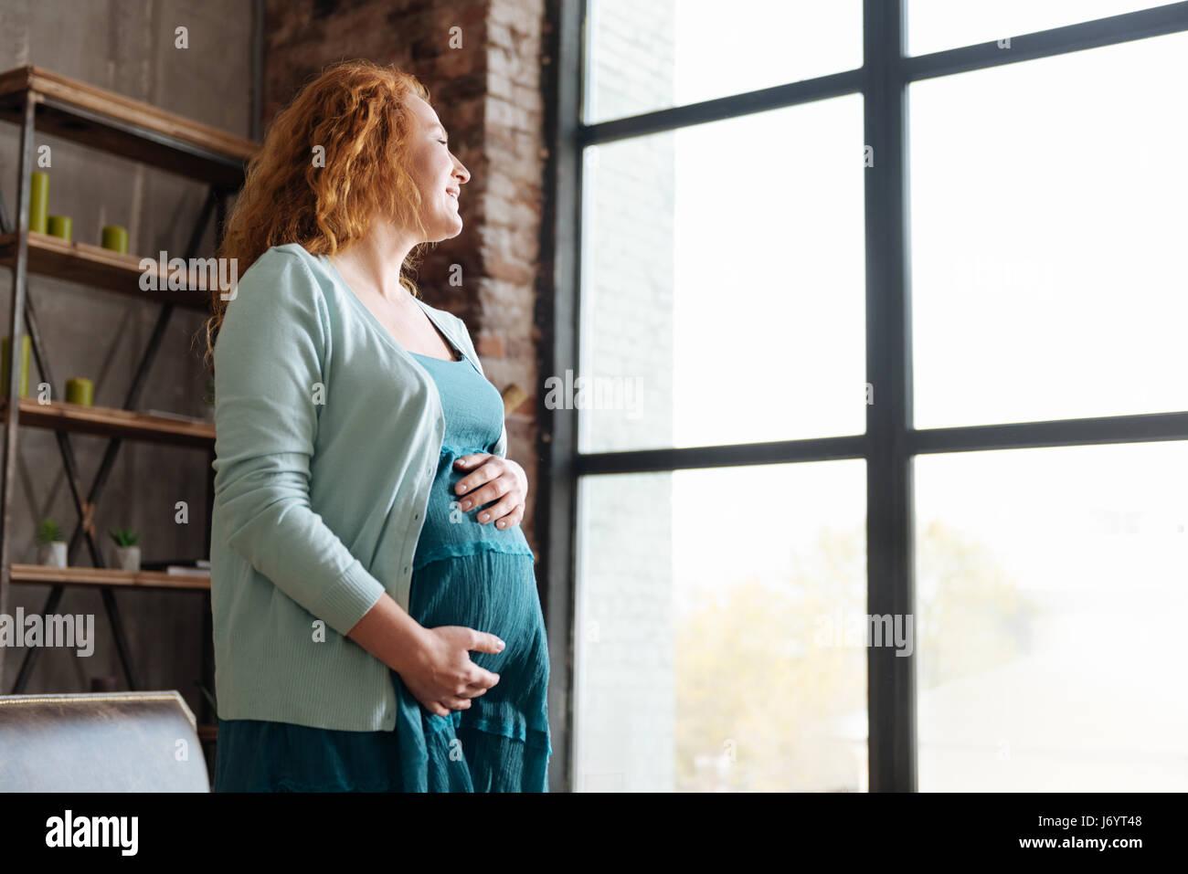 Sorridente madre-essere a guardare fuori dalla finestra Immagini Stock