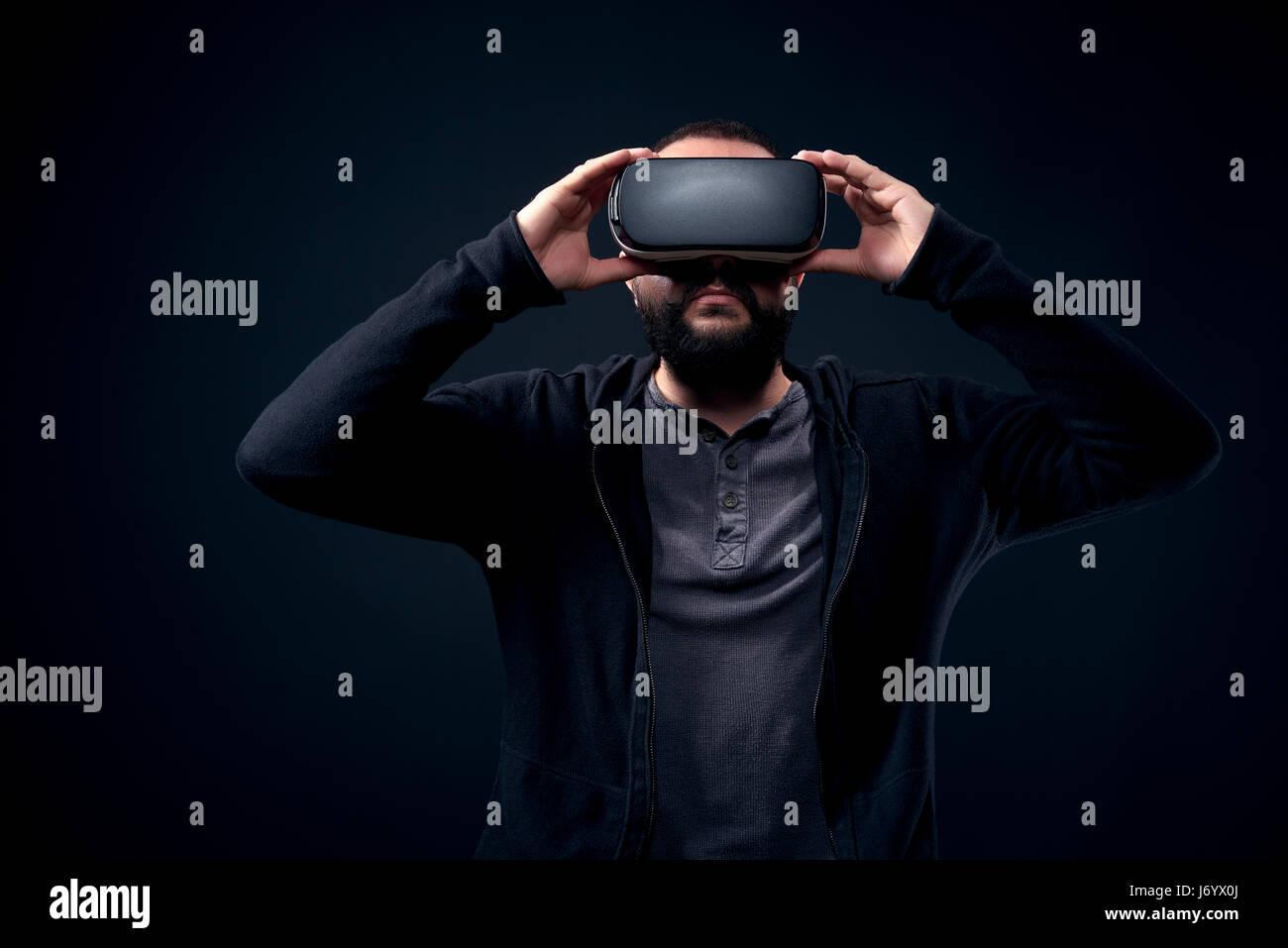 Tanga giovane uomo barbuto che indossa la realtà virtuale gli occhiali. Sfondo nero studio concetto vr Immagini Stock