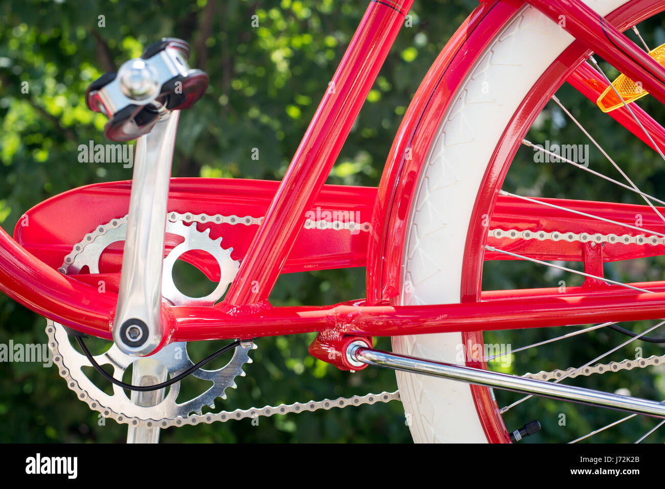 Parte del rosso telaio bicyle, la catena e il pedale su sfondo verde, il concetto di uno stile di vita sano e mezzi Immagini Stock