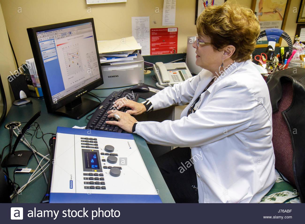 Miami Florida HEARx HearUSA Hearing Aid office provider donna ispanica computer tecnico sul posto di lavoro lavoro Immagini Stock