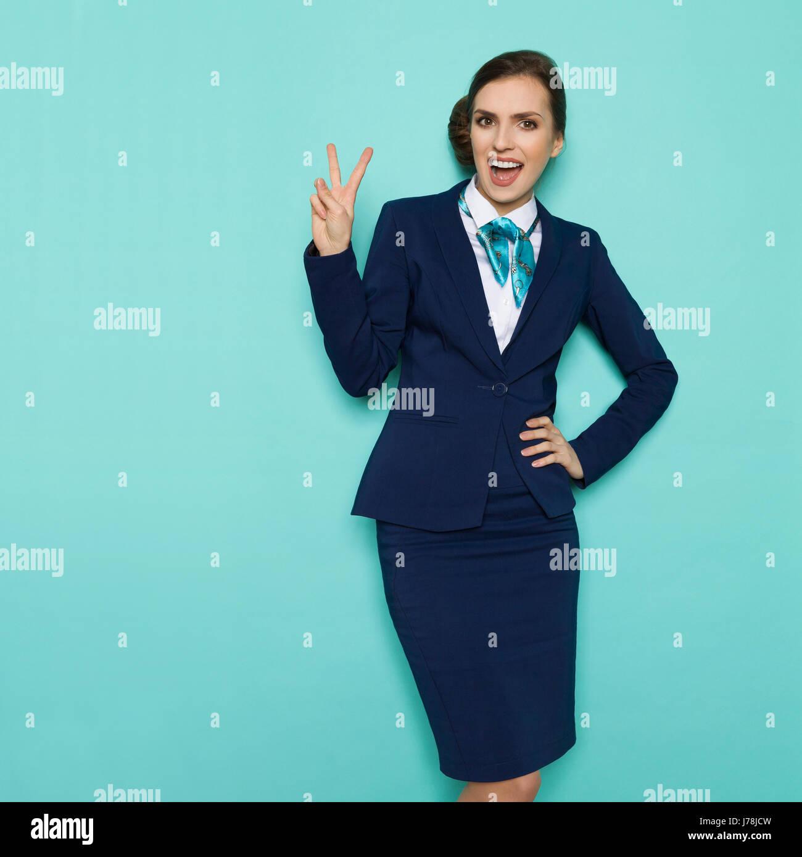 Hostess felice in blu abbigliamento formale è che mostra la pace segno a mano, gridando e guardando la fotocamera. Immagini Stock
