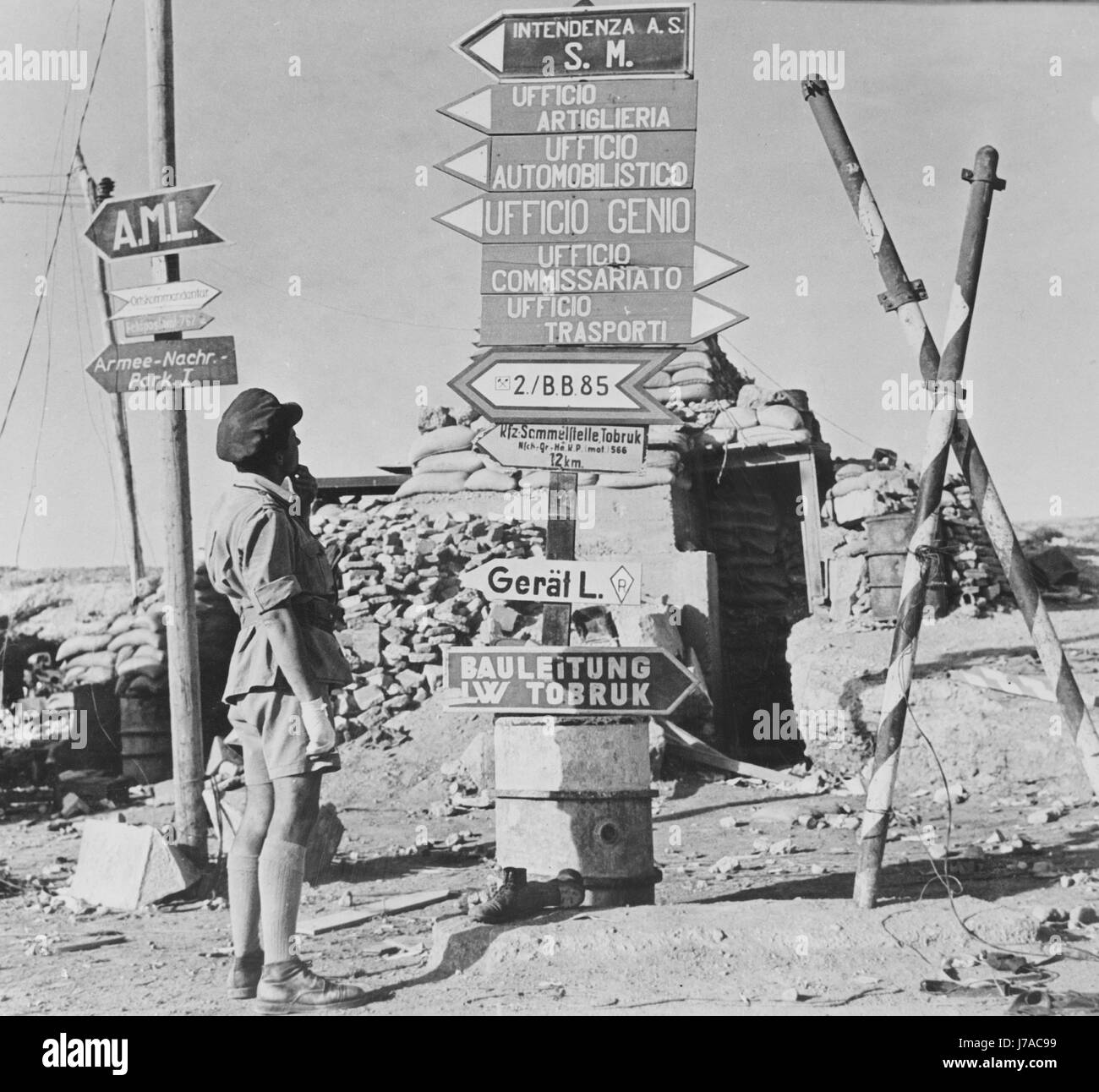 Firmare messaggi stampati in Italiano e Tedesco in corrispondenza di un angolo di strada a Tobruk, Libia, circa Immagini Stock