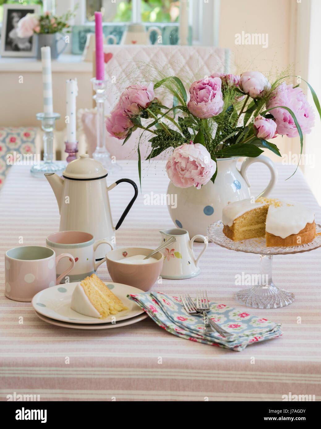 Pan di spagna, smalto teiera e peonie rosa sul tavolo rigato stoffa da Susie Watson Designs Immagini Stock