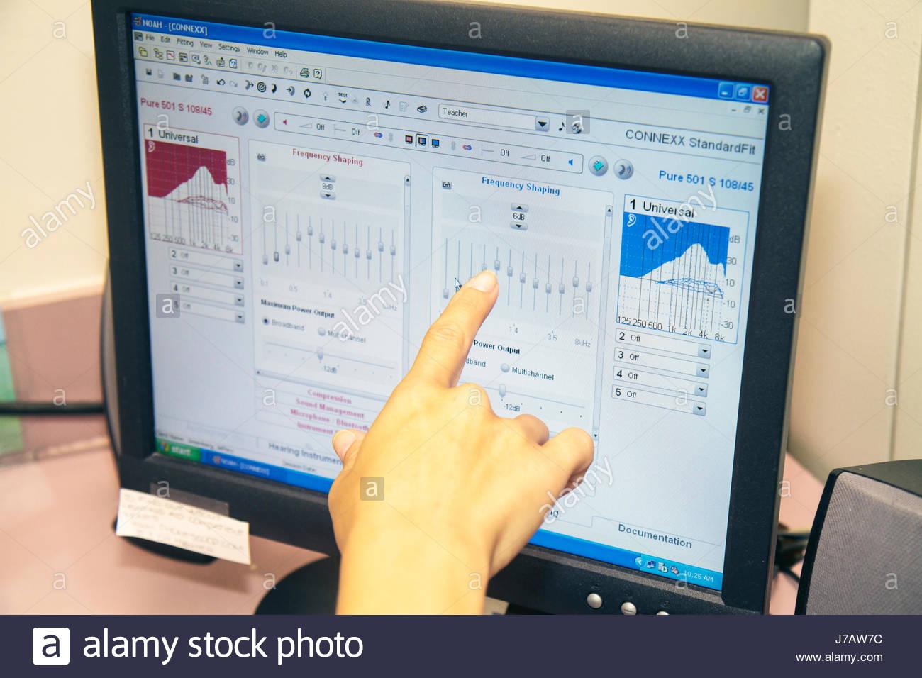 Miami Florida Aventura HearX Hearing Aid sala esame sul monitor di un computer di conformazione di frequenza di Immagini Stock