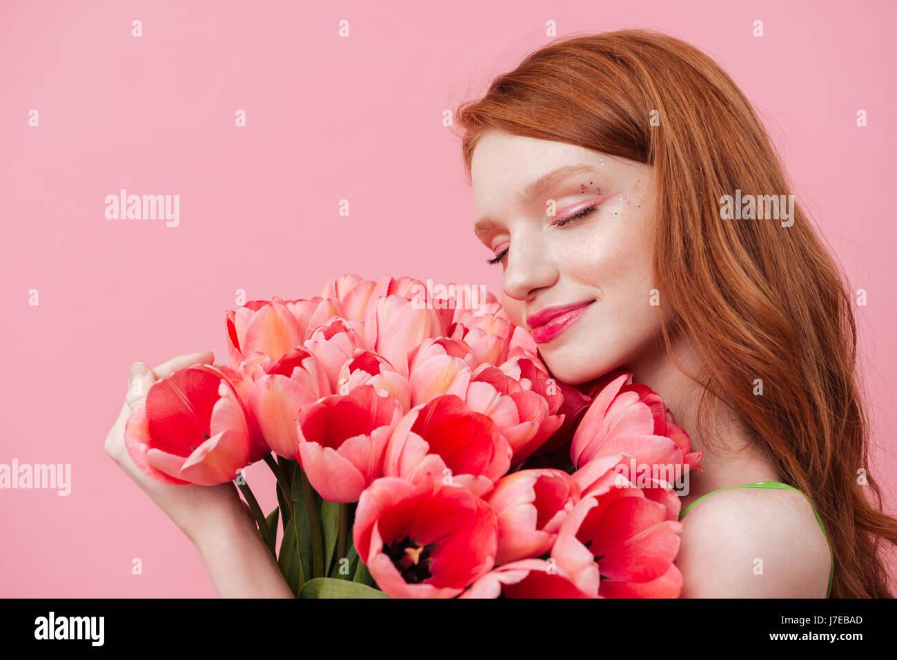 Giovane donna graziosa toccando e annusando con gli occhi chiusi fiori di colore rosa Immagini Stock
