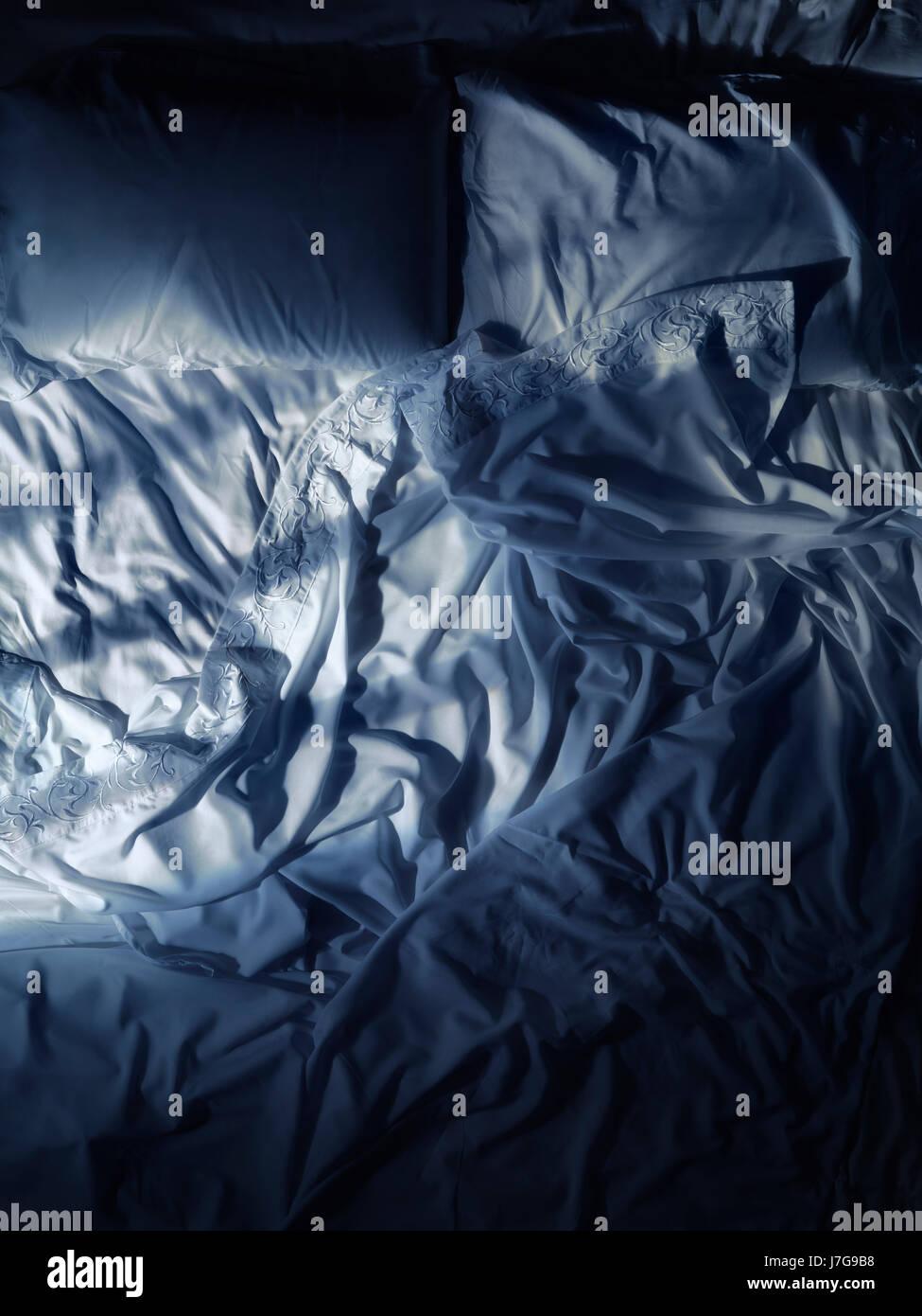 Disfatto letto vuoto, bianco lenzuola poco illuminata dalla luna di notte Immagini Stock