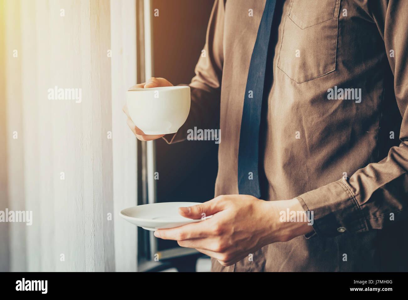 Giovane uomo d affari azienda tazza di caffè in ufficio in finestra. Immagini Stock