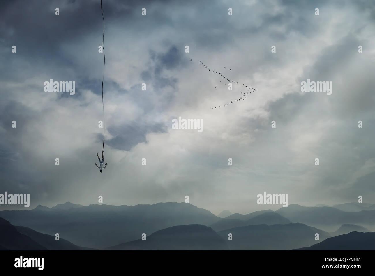 Giovane uomo che cadono dal cielo con una corda legata alla sua gamba come assicurazione di sicurezza. Base jump, Immagini Stock