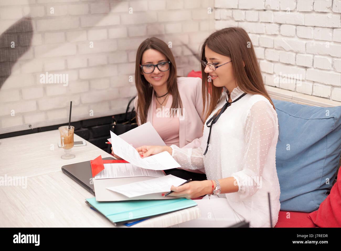 Due giovani donne sorridente in un incontro di affari. Risolvere i problemi relativi alle aziende Immagini Stock