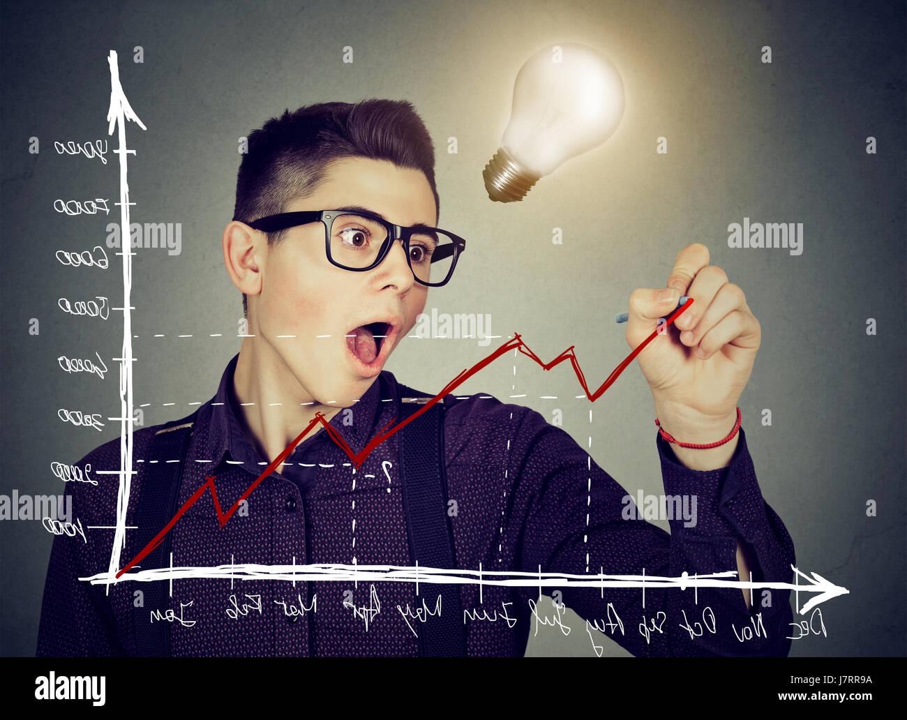 Giovane uomo d affari charting un positivo trend grafico ha idea brillante Immagini Stock