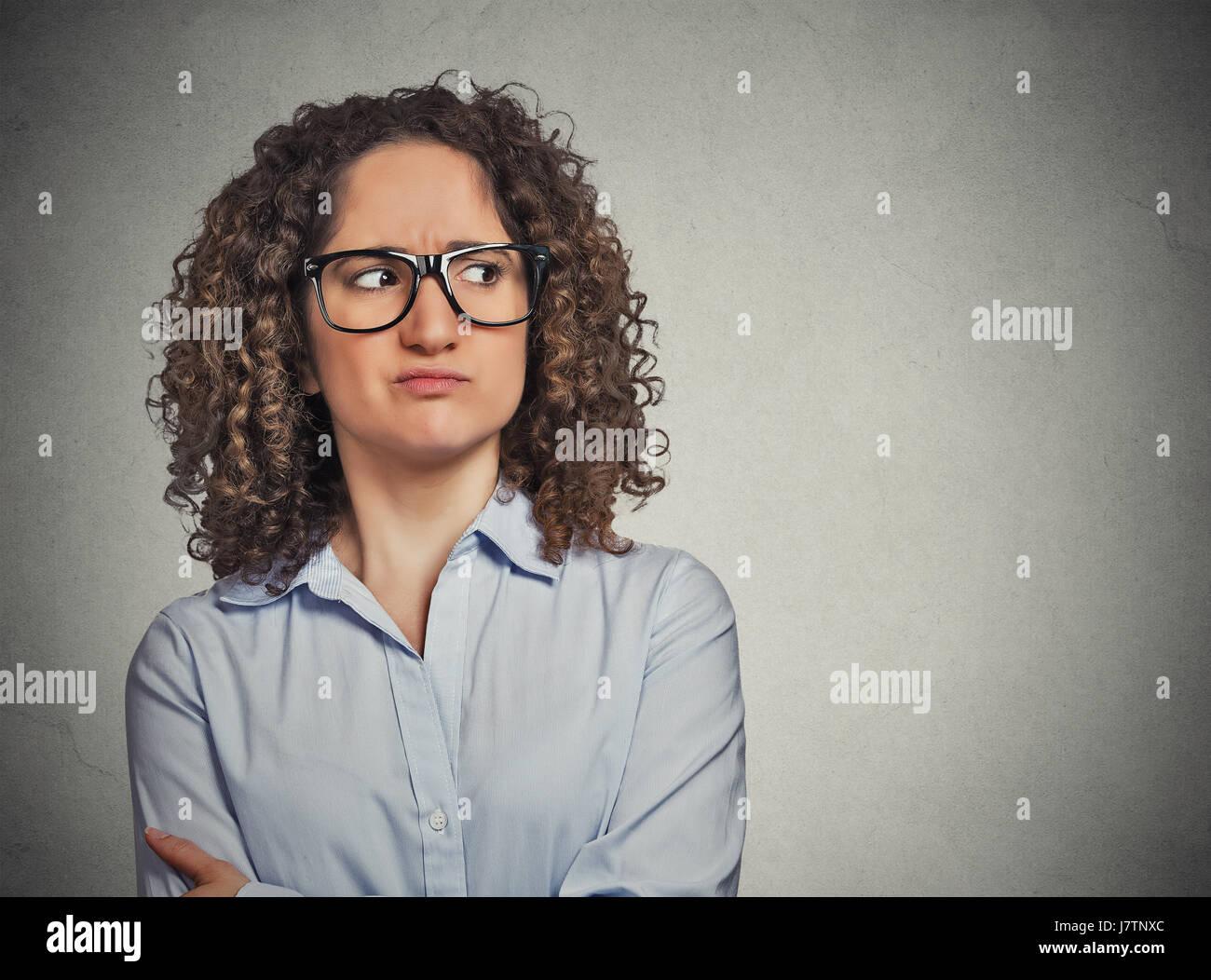 Orinato sospettoso giovane donna con gli occhiali guardando dal lato isolato sul muro grigio Sfondo. Faccia negativa Immagini Stock