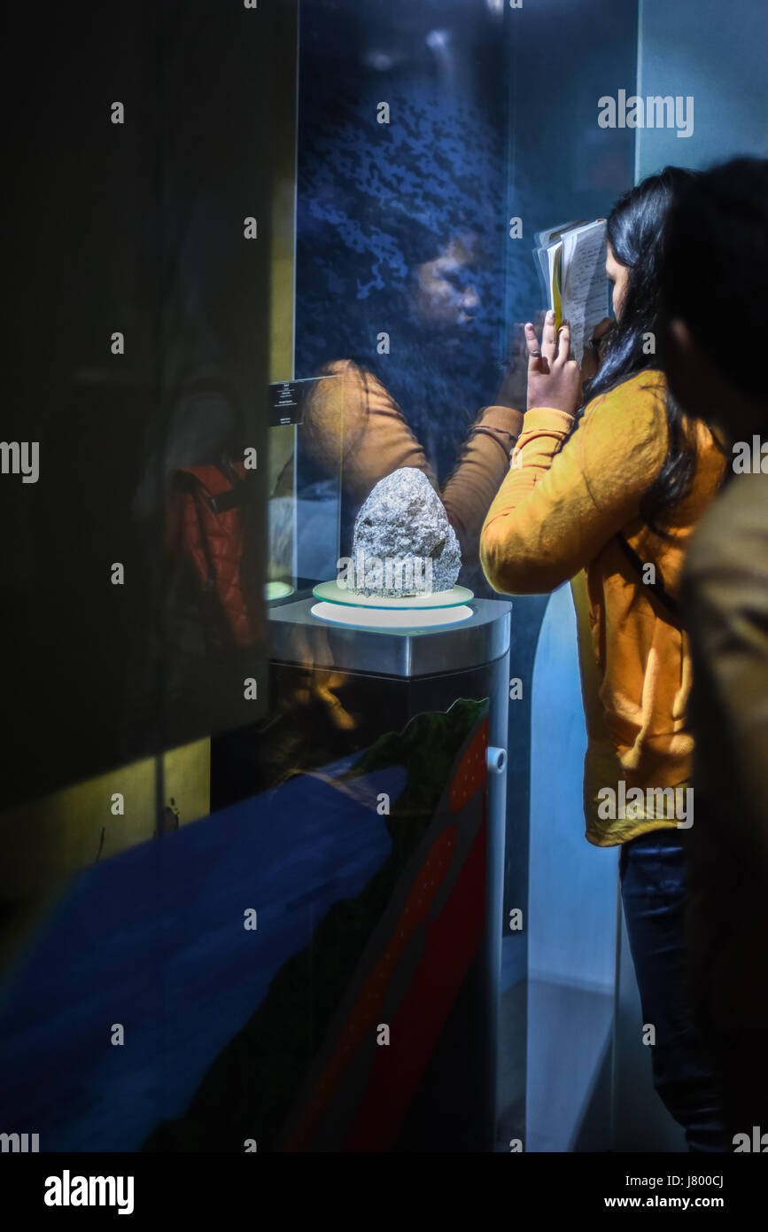 Studentessa rendendo note sull'oggetto geologico al Museo di geologia, Bandung, Indonesia. Immagini Stock
