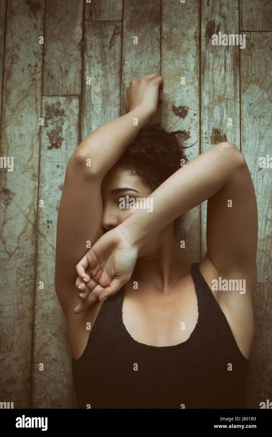 Spaventata donna nascondendo la faccia recante sul pavimento Immagini Stock