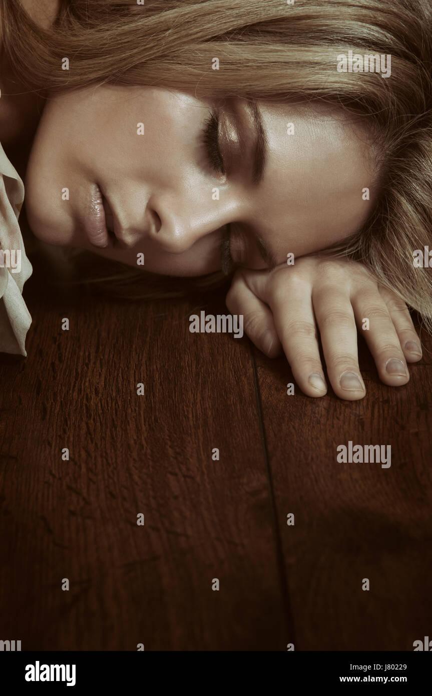 Stanco giovane donna dormire sul pavimento Immagini Stock