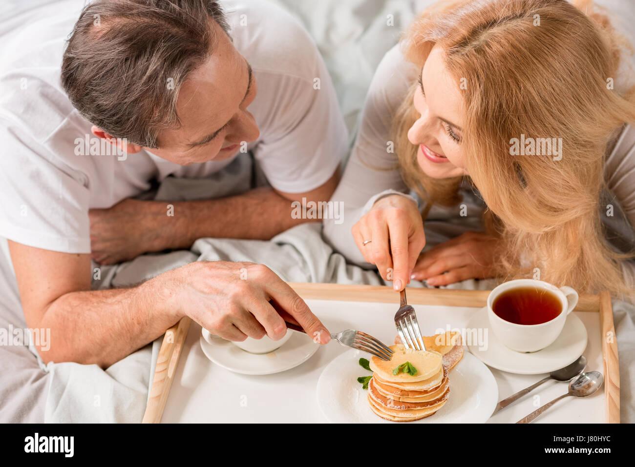 Felice Coppia di mezza età avente insieme per la prima colazione a letto Immagini Stock