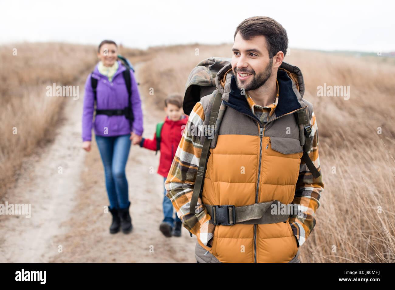 Close-up ritratto di Giovane uomo con la moglie e il figlio con lo zaino in spalla in area rurale a nuvoloso giorno Immagini Stock