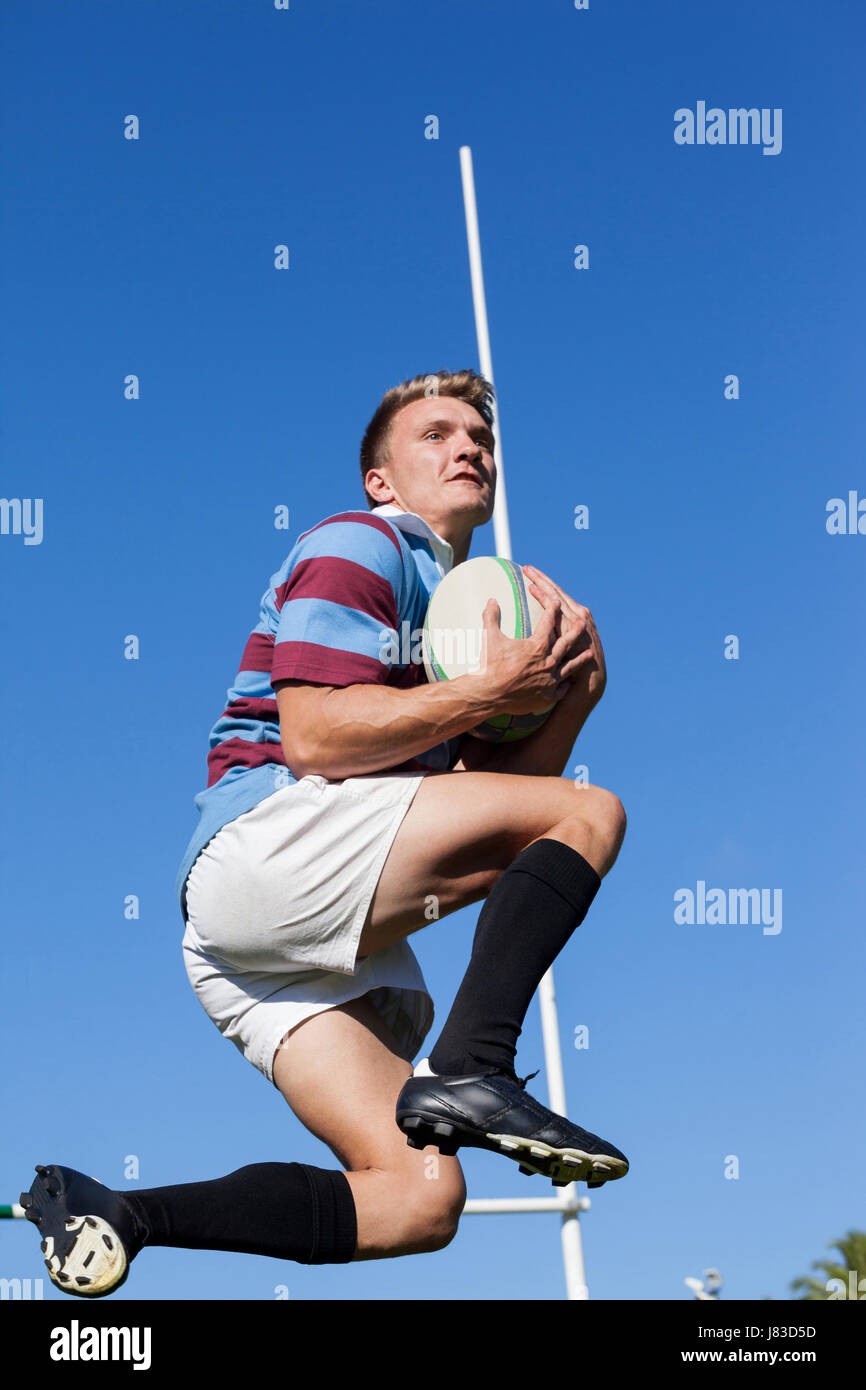 Basso angolo vista del giocatore di rugby cattura la sfera contro il cielo blu chiaro Immagini Stock