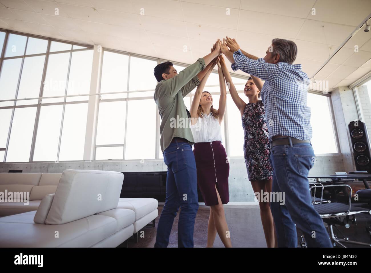 La gente di affari alzando le mani insieme a Office creative Immagini Stock