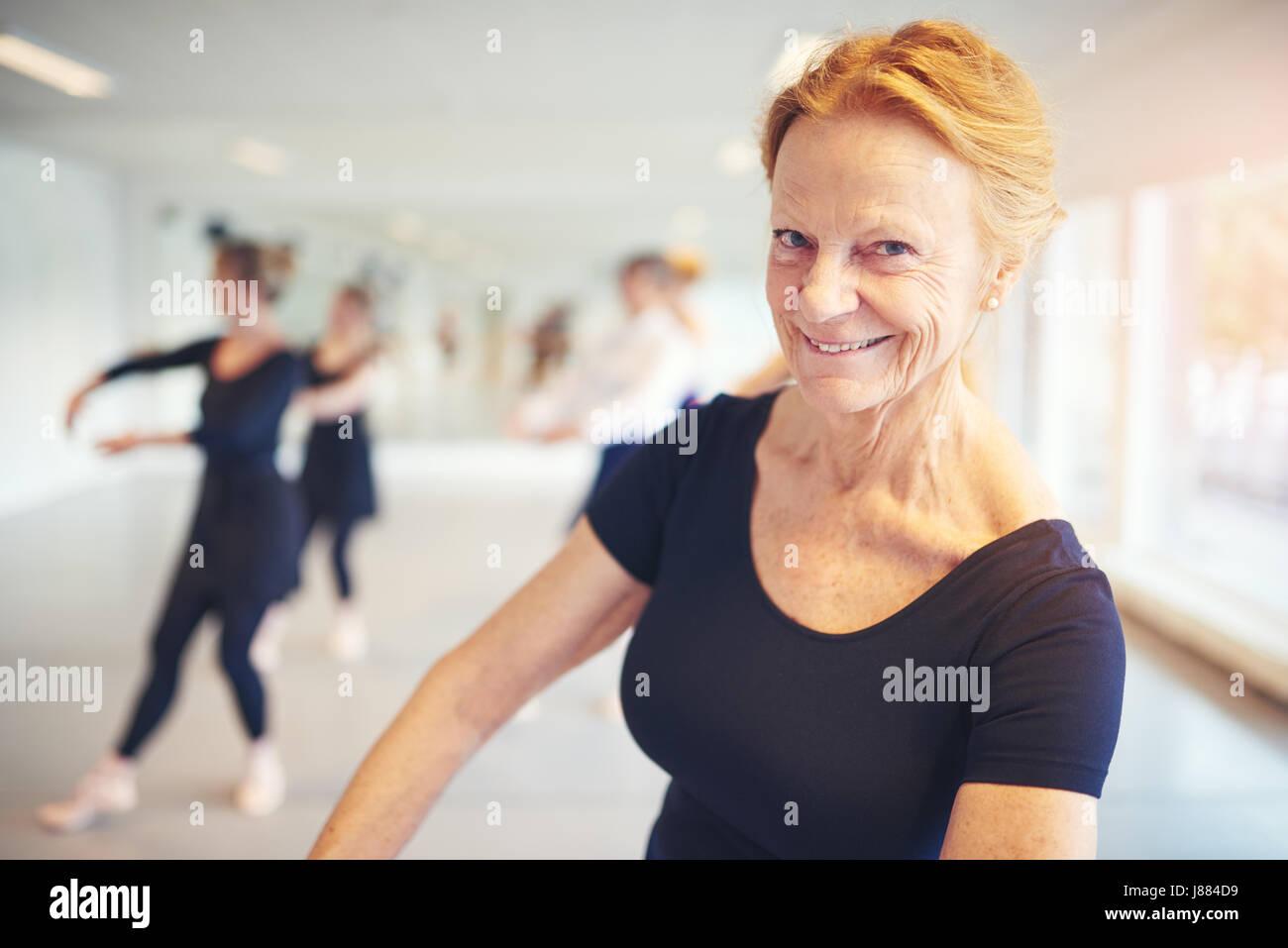 Donna matura sorridente e guardando la telecamera durante l'esecuzione di balletto in classe. Immagini Stock