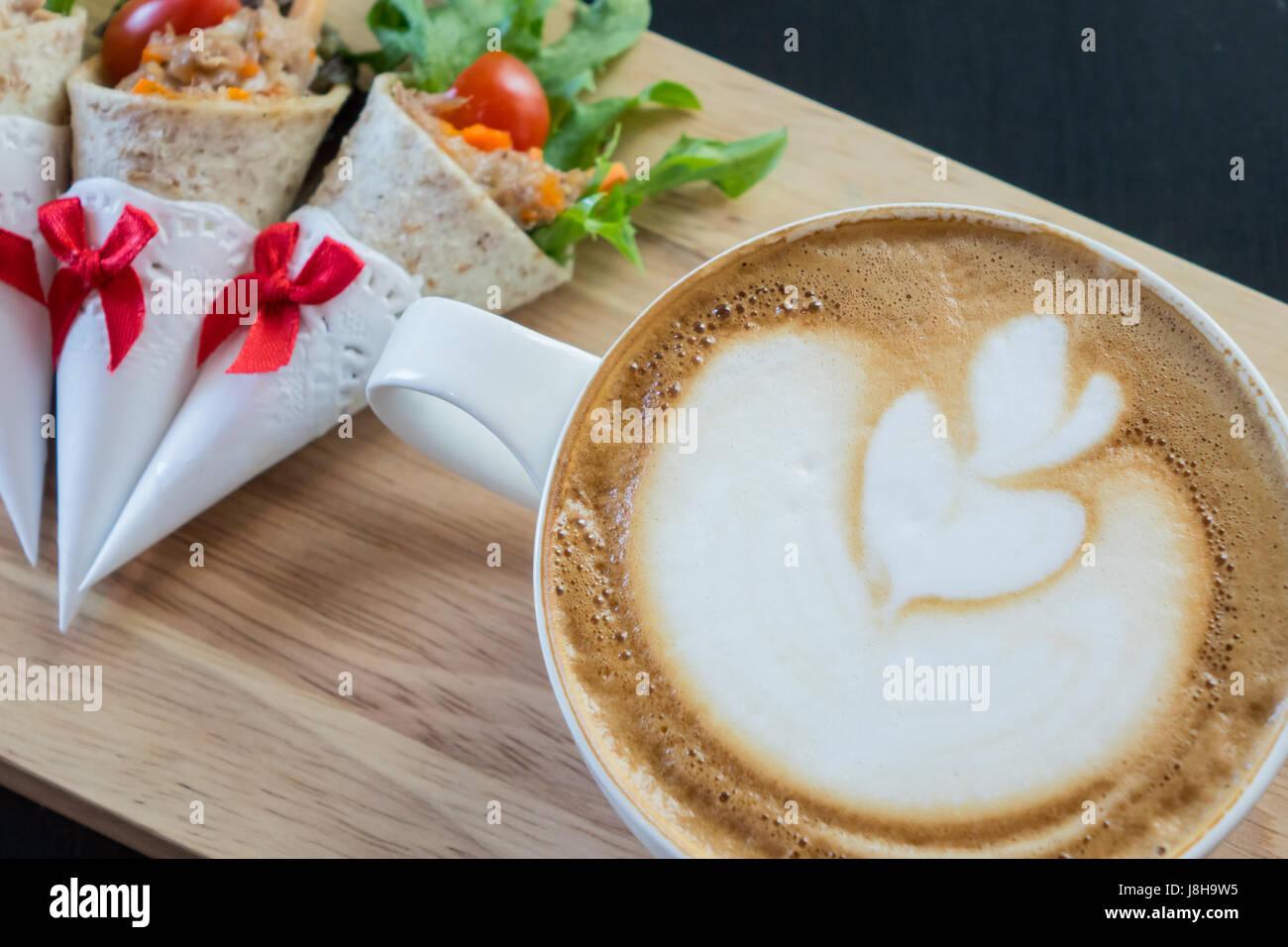 Latte art caffè con panini, tonno wrap. Immagini Stock