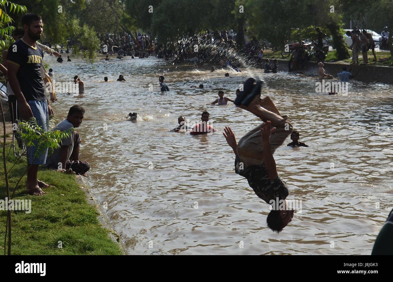 La popolazione pakistana tenendo bagno nellacqua del canale per