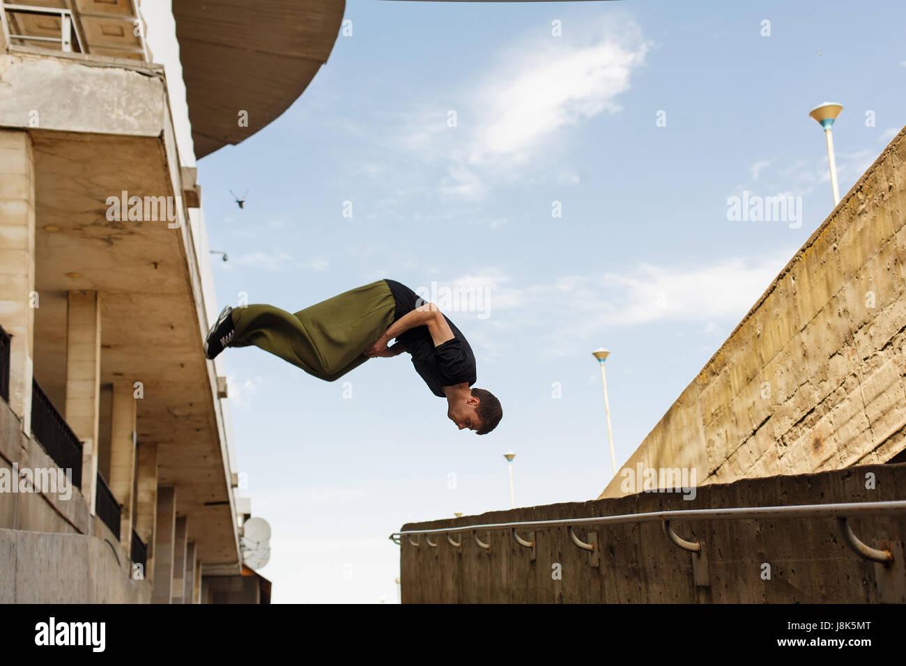 Giovane uomo back flip. Parkour nello spazio urbano. Sport in città. Attività sportive all'aperto. Immagini Stock
