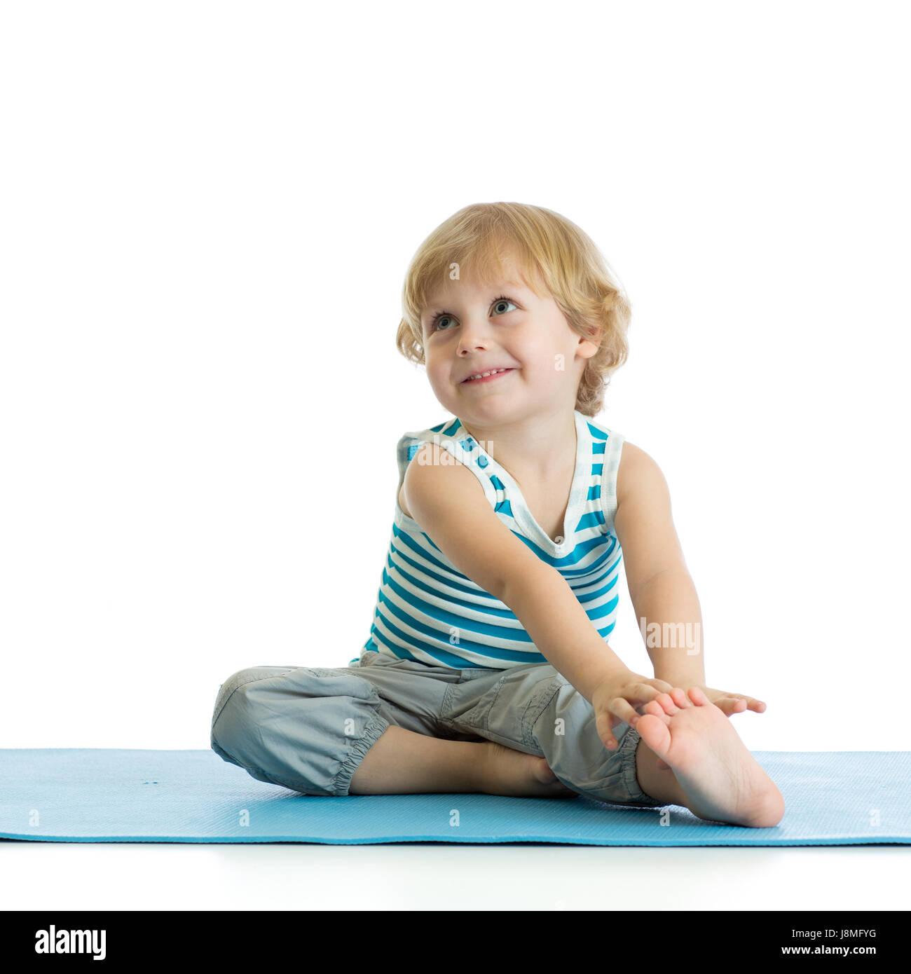 Ragazzo bambino la pratica dello yoga, stretching in esercizio. Kid isolate su sfondo bianco Immagini Stock