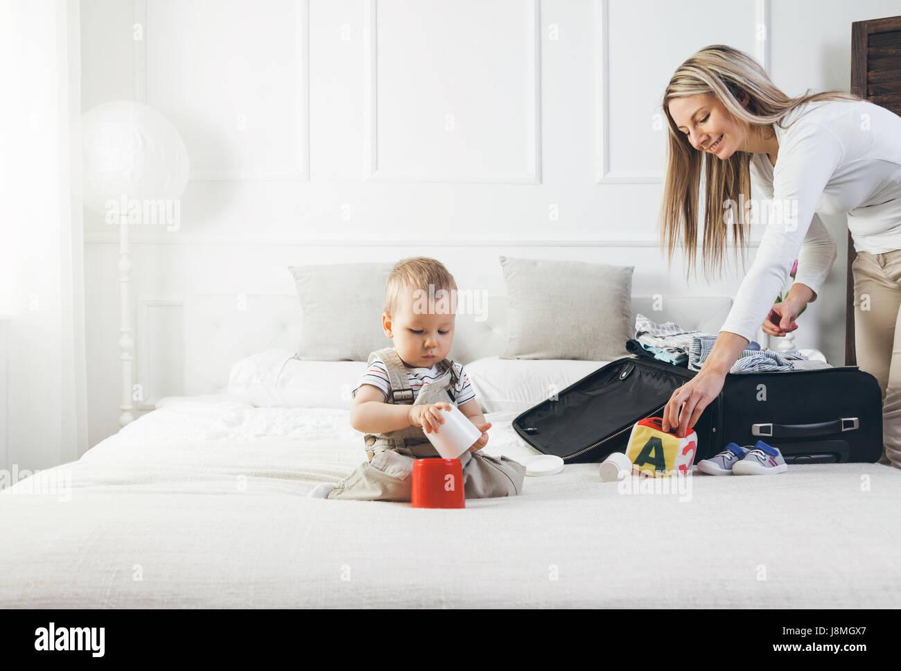 Viaggiare con i bambini. Felice madre con il suo bambino abiti di imballaggio per le proprie vacanze Immagini Stock