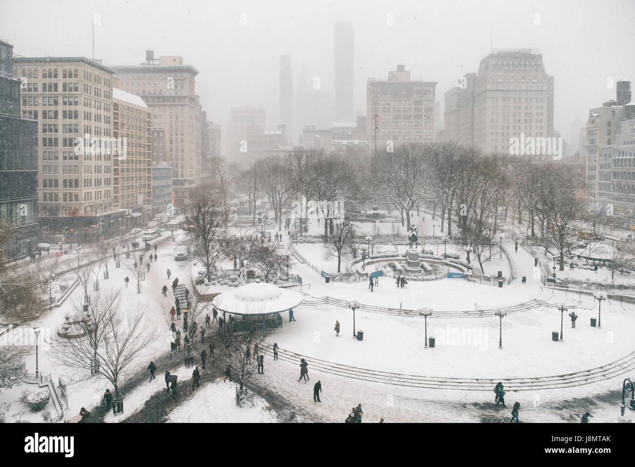 Nevoso inverno scena con sentieri a sinistra da pedoni nella neve in Union Square come una bufera di neve si impadronisce Immagini Stock