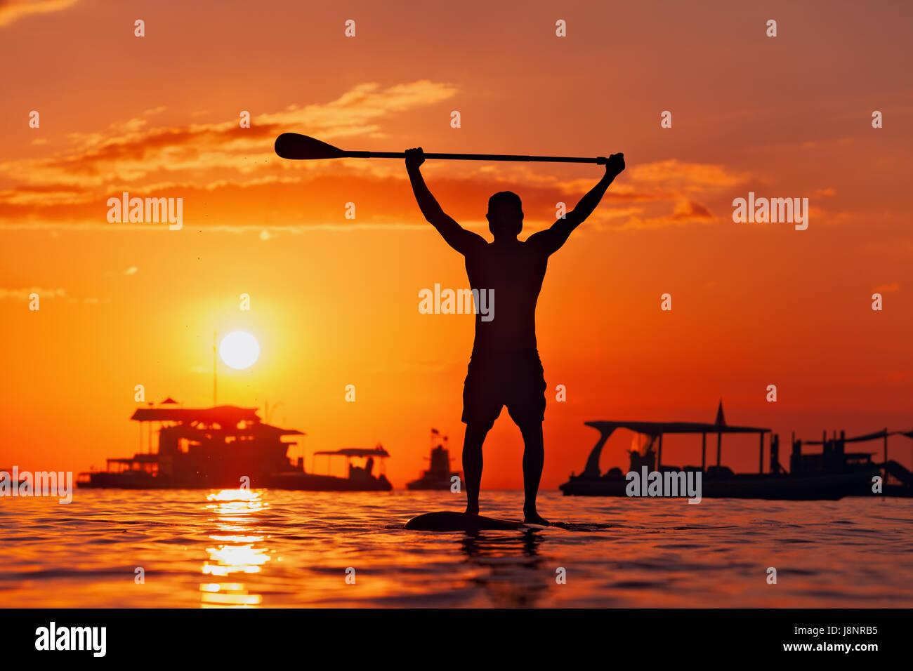 Active paddle boarder. Nero silhouette al tramonto del giovane atleta paddling in stand up paddleboard. Uno stile Immagini Stock