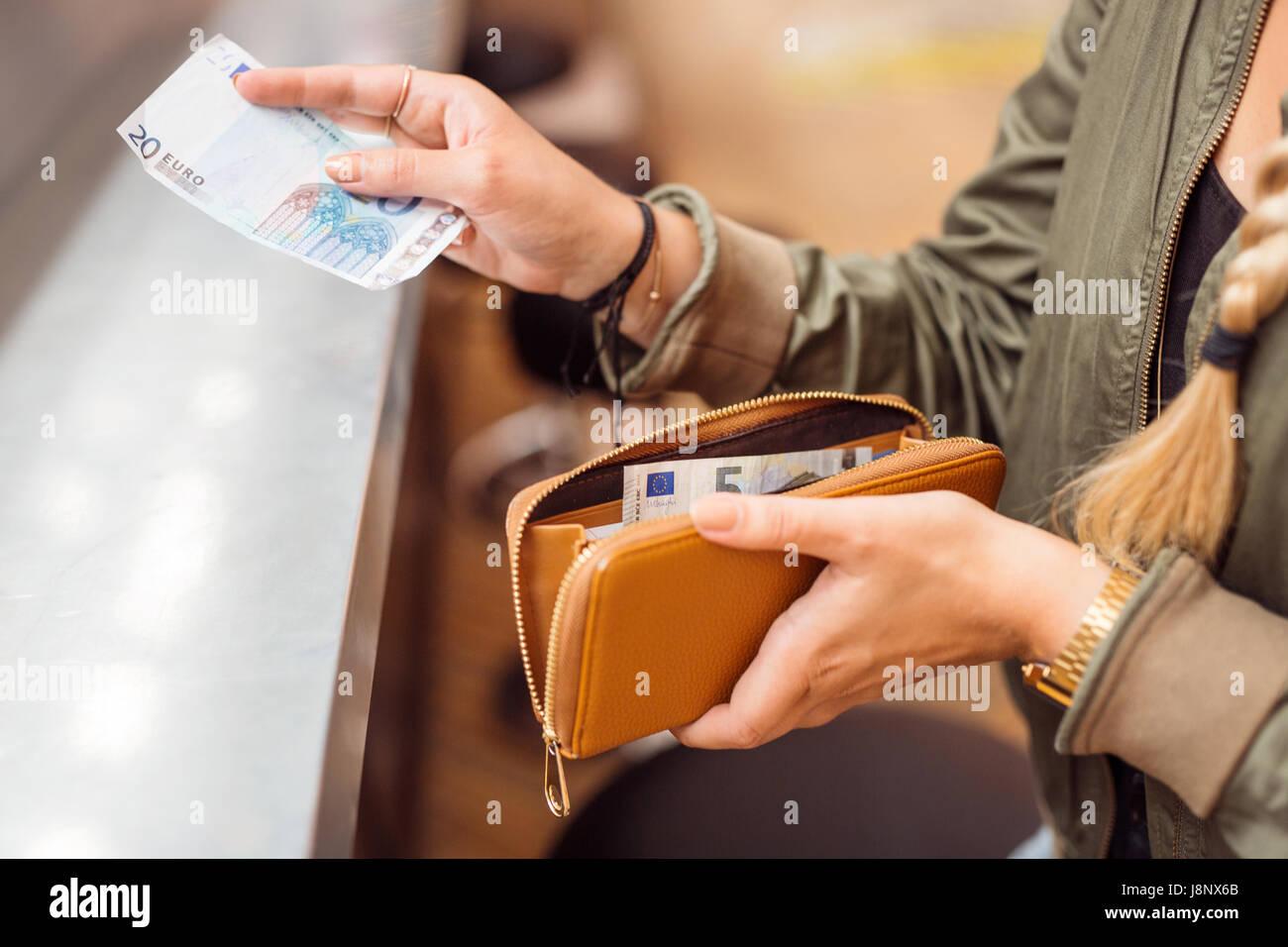 Donna con pagamento in contanti presso il bar Foto Stock