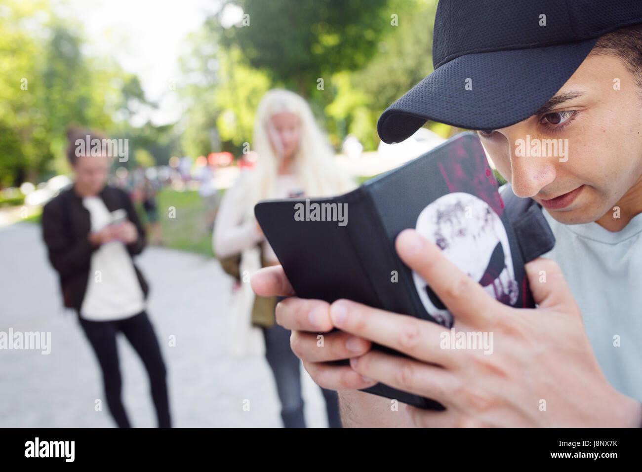 Gruppo di amici a giocare gioco basato sulla realtà aumentata con i telefoni cellulari Foto Stock
