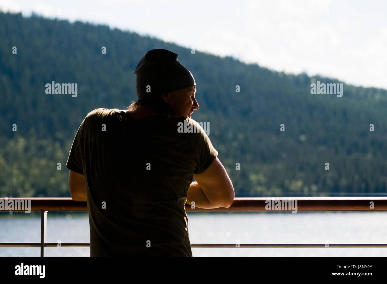 Uomo appoggiato su parapetto Foto Stock