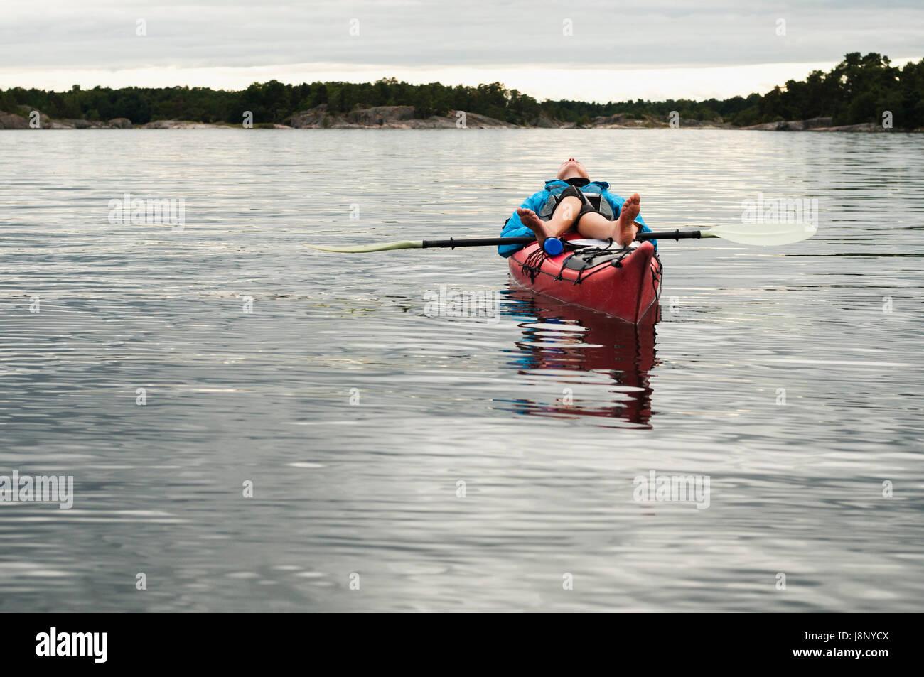 Donna sdraiata sul kayak Foto Stock