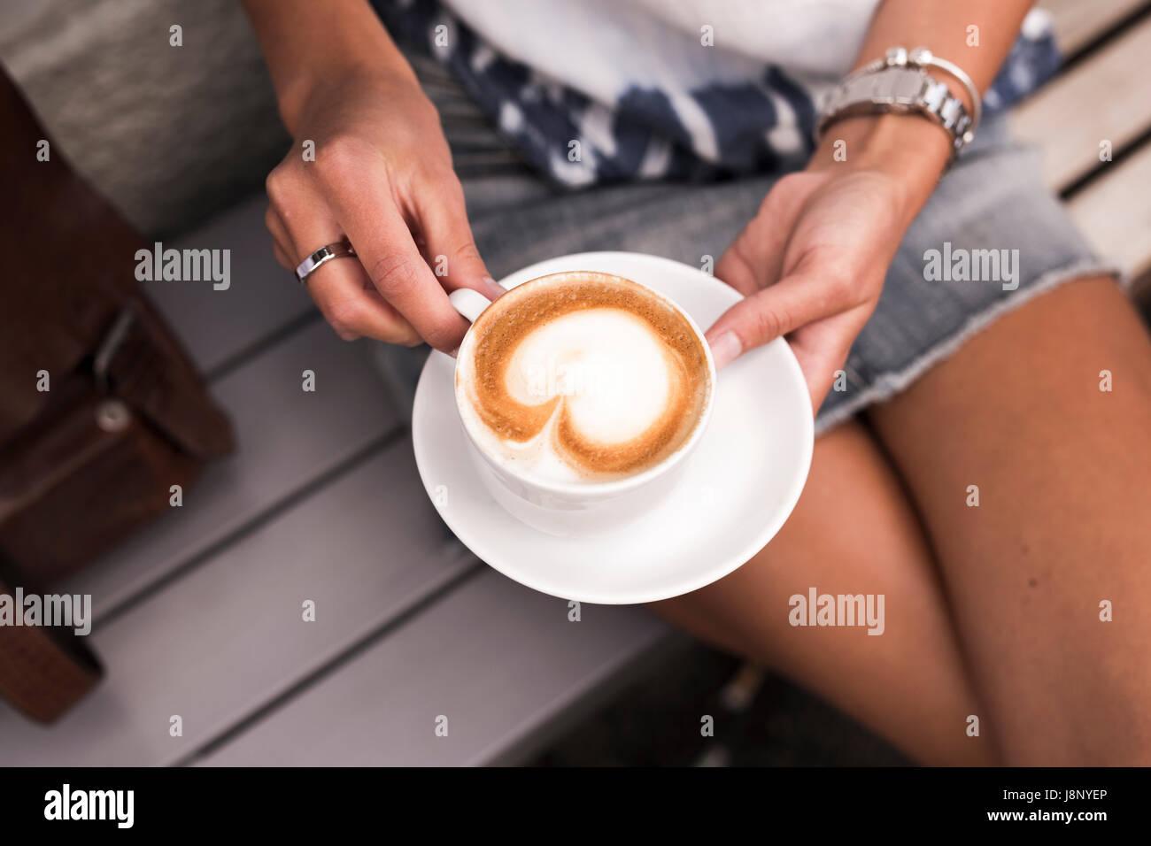 Donna che mantiene tazza da caffè con cappuccino Foto Stock