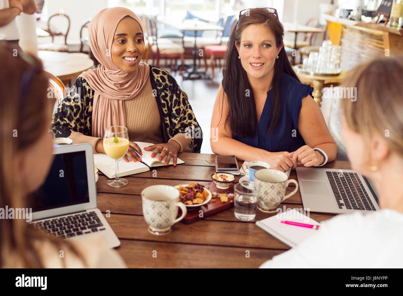 Imprenditrici lavorando durante il pranzo in ristorante Foto Stock
