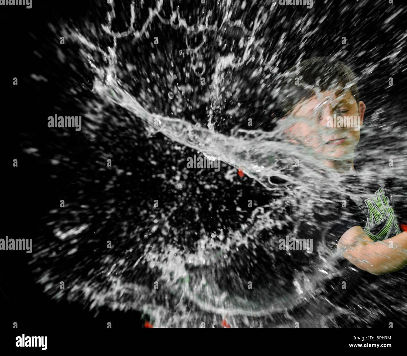 Ragazzo giovane si disperde acqua al centro, a destra e a sinistra dopo aver colpito un palloncino di acqua con Immagini Stock